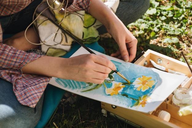 Close das mãos de uma mulher pintando flores brilhantes a óleo ao ar livre