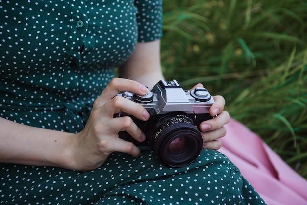 Close das mãos de uma mulher segurando uma câmera de filme vintage