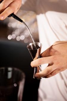 Close das mãos do barman servindo bebida alcoólica.