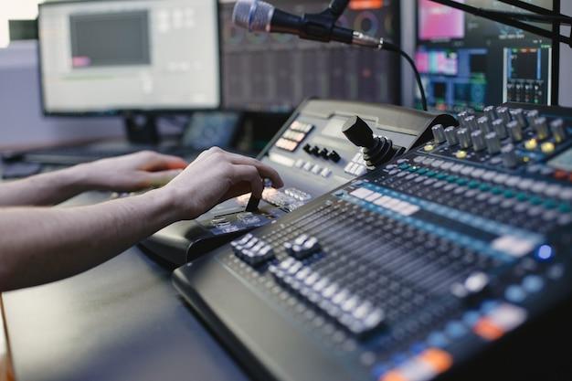 Close das mãos do engenheiro de som gravando música