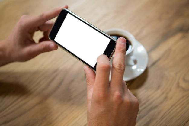 Close das mãos do homem fotografando café em um smartphone em uma cafeteria