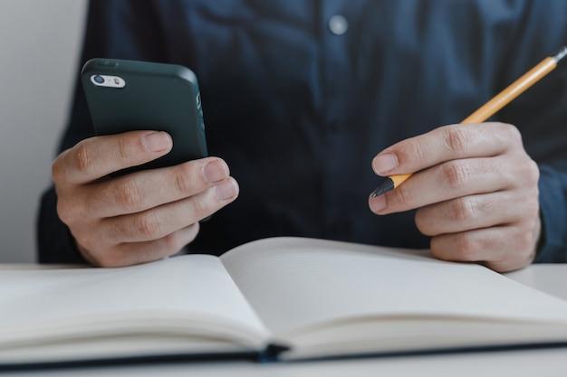 Close das mãos do homem segurando um telefone celular e um lápis entre os dedos.