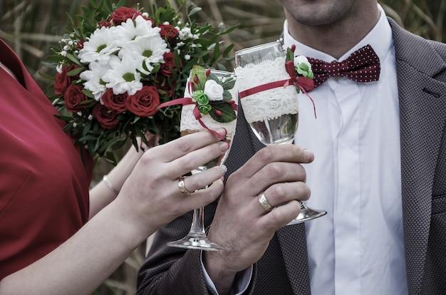 Close das mãos e copos de recém-casados com champanhe