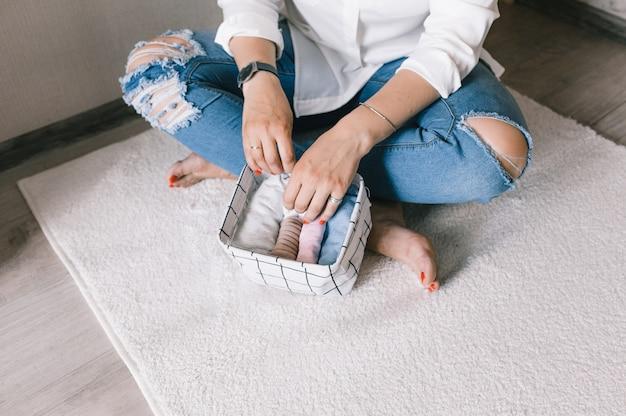 Close das mãos femininas dobrando lindamente as coisas em recipientes e caixas. o conceito de armazenamento adequado de acessórios e roupas íntimas no armário