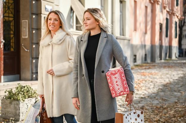 Close das mulheres segurando sacos de papel e presentes enquanto caminhavam no beco