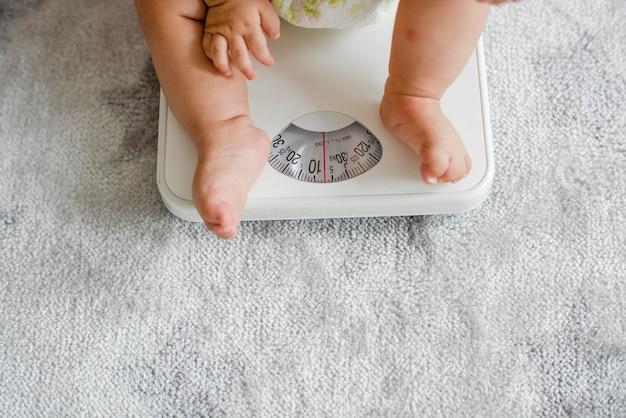 Close das pernas de um bebê em uma balança