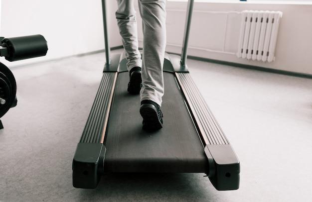 Close das pernas de um homem em uma esteira. treino cardio