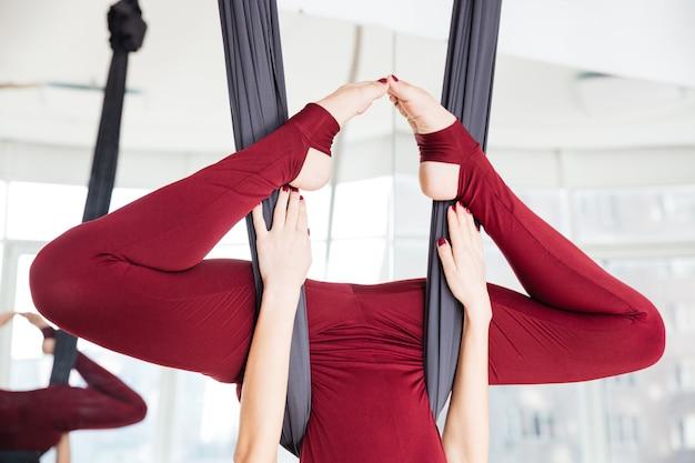 Close das pernas de uma esportista fazendo exercícios de ioga aérea em estúdio