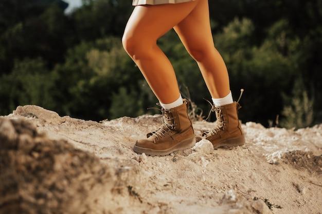 Close das pernas de uma jovem caminhando sobre as pedras nas montanhas