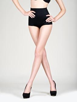 Close das pernas de uma jovem com sapatos pretos de salto alto