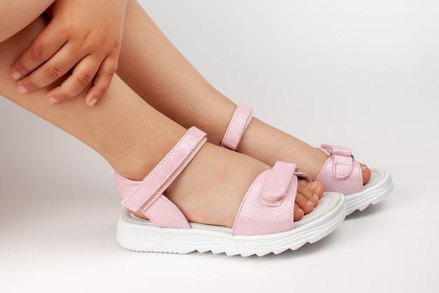 Close das pernas de uma menina abraçando os joelhos e sentada com sandálias rosa com fechos de velcro.
