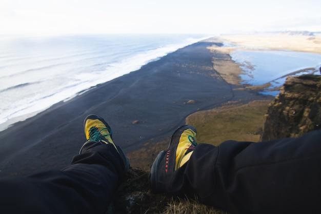 Close das pernas de uma pessoa sentada na rocha com o mar na islândia