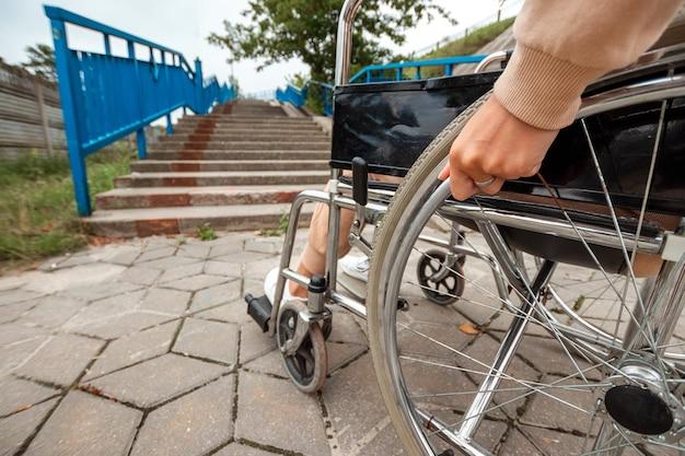 Close das pernas em uma cadeira de rodas. a menina está incapacitada. o conceito de cadeira de rodas, pessoa com deficiência, vida plena, paralítico, pessoa com deficiência, cuidados de saúde.