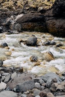 Close das rochas no rio da montanha lavadas rapidamente pela água corrente
