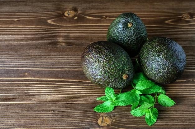 Close de abacates frescos grandes e orgânicos, isolado na mesa de madeira