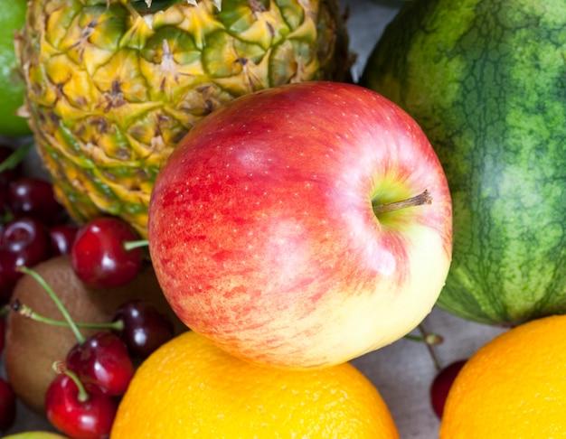 Close de abacaxi, maçã, laranja e outras frutas e bagas, foto de comida natural
