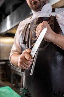 Close de açougueiro com avental de couro, afiando a lâmina de uma faca de cozinha usando uma vara de polir