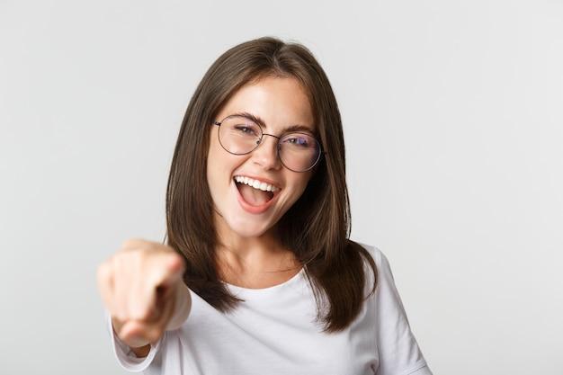 Close de alegre linda garota de óculos, sorrindo, apontando o dedo para a câmera