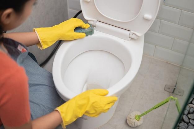 Close de alguém usando luvas limpando o banheiro com uma esponja no banheiro