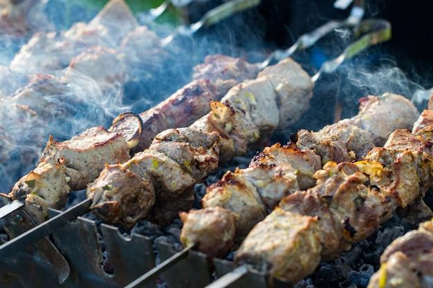 Close de alguns espetos de carne grelhados em um churrasco.