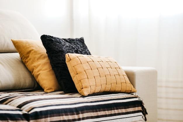 Close de almofadas pretas e amarelas em um sofá branco