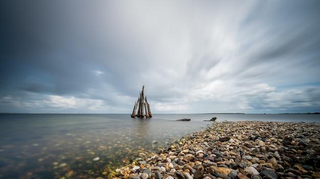 Close de alto ângulo de pedras à beira-mar levando ao mar calmo
