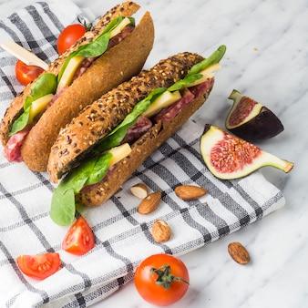 Close de amêndoas; tomate cereja; fatias de figo e saudáveis cachorros-quentes com guardanapo xadrez sobre fundo branco