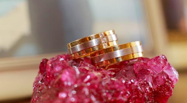 Close de anéis de casamento em um romance dourado de fundo padrão