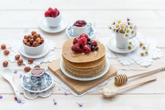 Close de ângulo alto de panquecas vegan cruas com mel e frutas