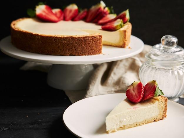 Close de ângulo alto de um cheesecake de morango em um prato branco e um fundo preto