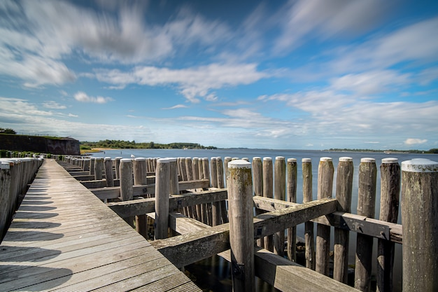 Close de ângulo alto de uma cerca de madeira à beira-mar levando ao mar