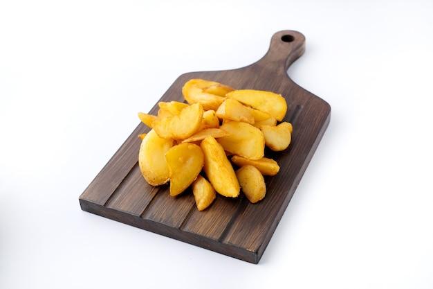 Close de batatas fritas caseiras em uma placa de madeira isolada no branco