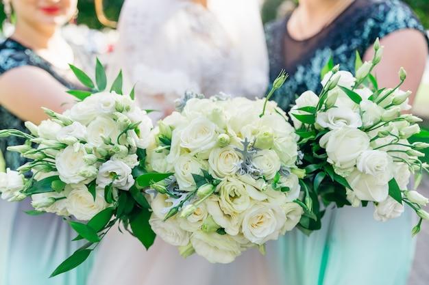 Close de buquês de noiva e damas de honra rosas brancas no fundo