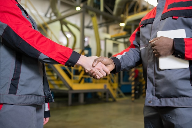 Close de capatazes multiétnicos irreconhecíveis em um aperto de mão uniforme em uma fábrica