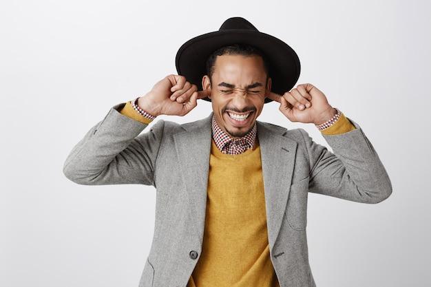 Close de cara afro-americano irritado e incomodado fechando os ouvidos com os dedos, não suporto música alta irritante