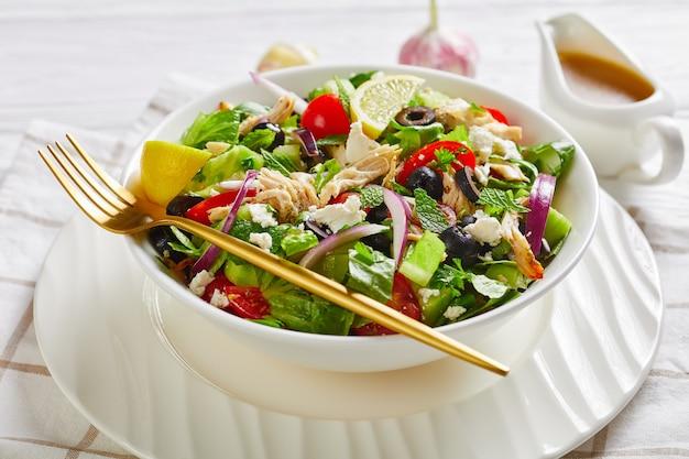 Close de carne de frango desfiada, azeitonas, cebola roxa, tomate, pepino, hortelã, salada de alface polvilhada com queijo feta esmigalhado em uma tigela branca, vista panorâmica de cima