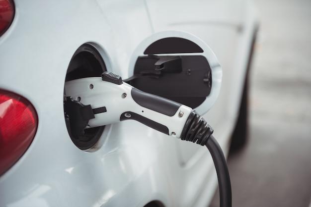 Close de carro sendo carregado com carregador elétrico