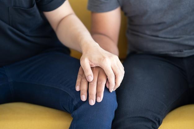 Close de casal gay lgbt segurando a mão no colo