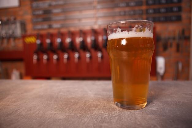Close de cerveja light em copo no balcão de cervejaria