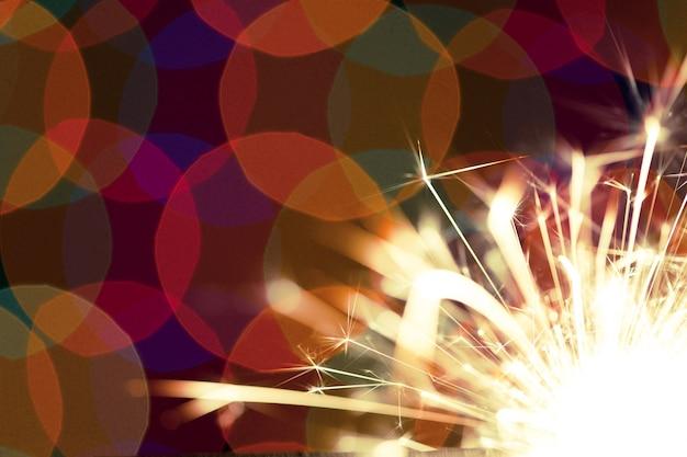 Close de círculos coloridos e fogo laranja brilhante de uma vela acesa ou saudação brilha no escuro. conceito de celebração de ano novo e natal. conceito de aniversário. copyspace