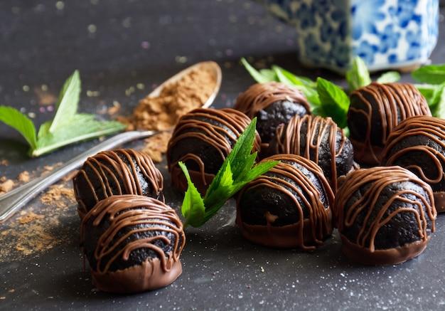 Close de colher de bombons de chocolate caseiros com sobremesa doce de cacau em pó