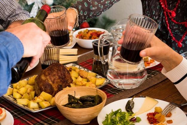 Close de comida e mãos tomando vinho - jantar familiar ou almoço - celebrando algo