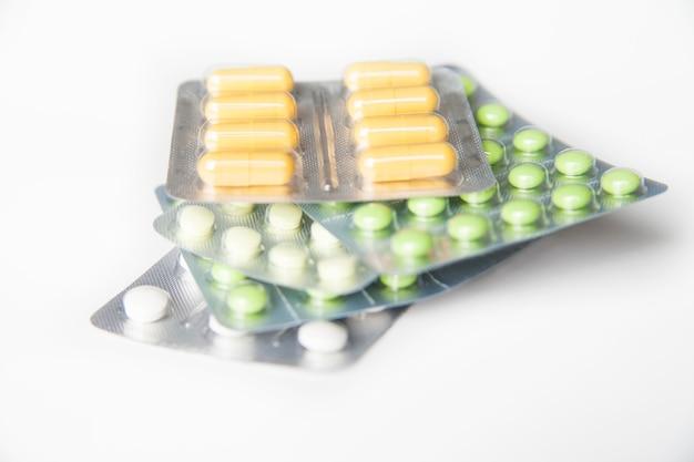 Close de comprimidos verdes e brancos em bolhas em fundo branco