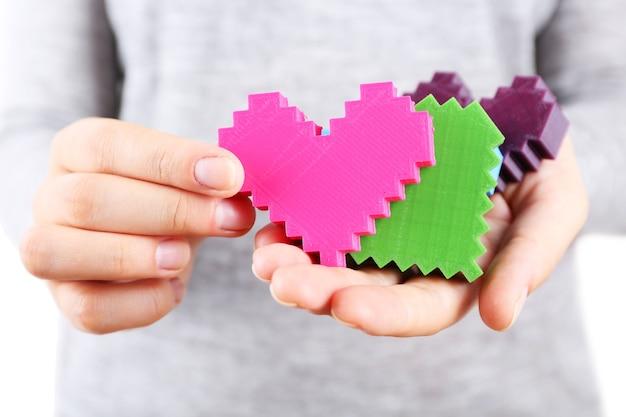 Close de corações de quebra-cabeça de plástico em mãos femininas