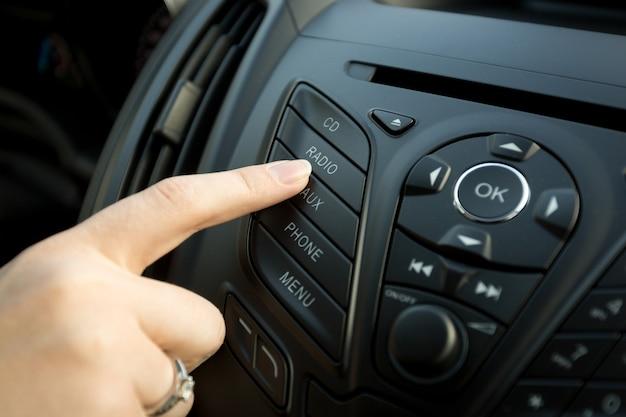 Close de dedo feminino pressionando o botão de rádio no painel de controle do carro