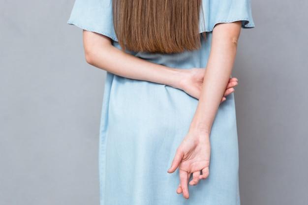 Close de dedos cruzados atrás das costas da mulher