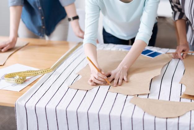 Close de delicadas mãos femininas pressionando um padrão em um pedaço de tecido listrado e traçando-o com lápis
