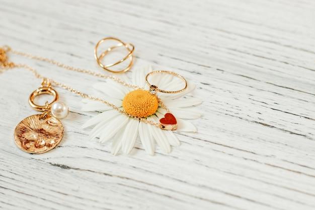 Close de delicadas margaridas com joias de ouro. correntes, pingentes, anéis em um suporte.