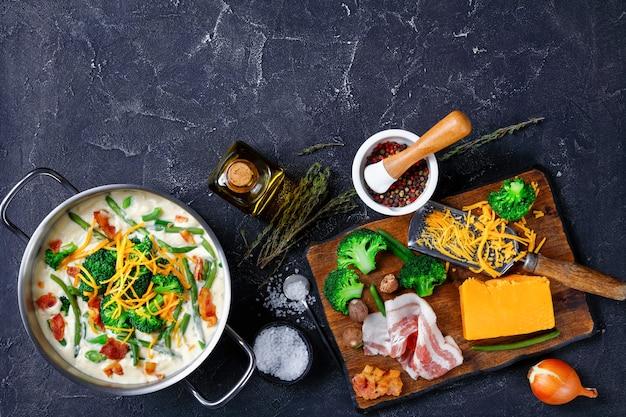 Close de deliciosa sopa de creme com brócolis, feijão verde, bacon frito e queijo cheddar ralado em uma caçarola de metal o