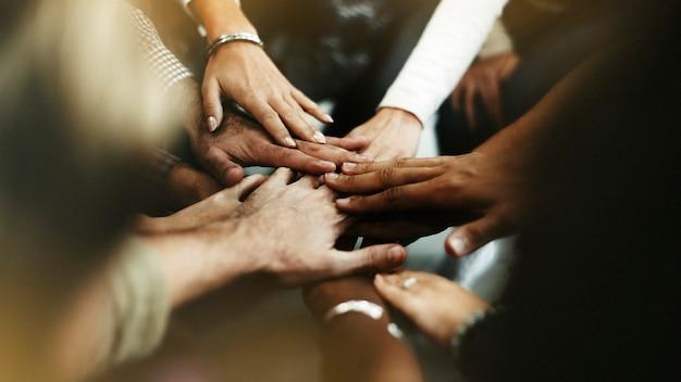 Close de diversas pessoas dando as mãos